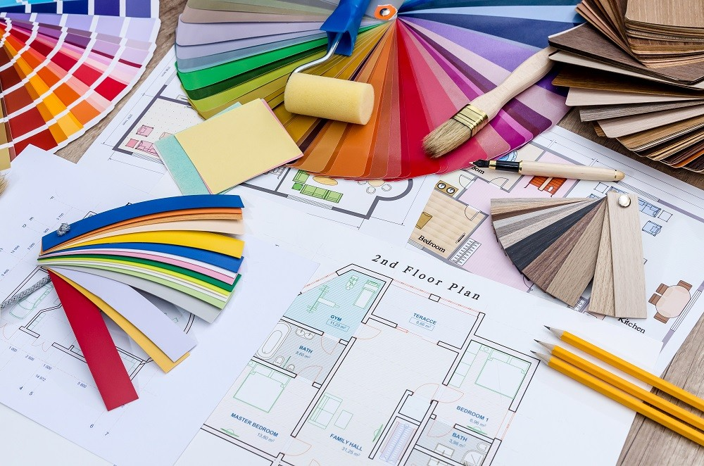 On the table lay the house plan, colored and wooden designs, work tools